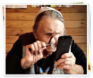 Фото, человек смотрит на экран смартфона через лупу